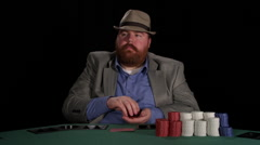 Poker player handles his chips as he contemplates and then tosses in a bet Stock Footage