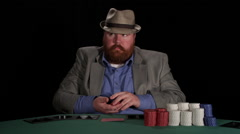 Poker player handles his chips as he contemplates and then places bet Stock Footage
