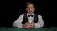 Dealer shuffles a deck of cards then deals them - stock footage