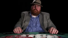 Poker player plays with chips in the pot as he laughs maniacally over them Stock Footage