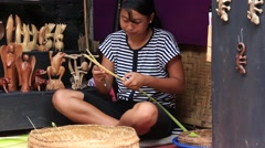 Girl make baskets for balinese offerings to gods in a temple, Bali, Indonesia Stock Footage