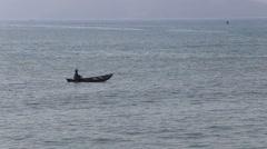 vietnamese fisherman drifts in boat rolling in sea waves - stock footage