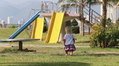 Blonde girl in Ukrainian blouse walks to slide on play ground Stock Footage