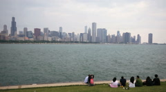 People family relaxes by Lake Michigan and view Chicago skyline on cloudy day Stock Footage