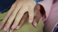 4K Close up on hands of young mixed ethnicity couple holding hands tightly - stock footage