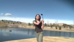 Attractive young girl smiling swinging golf club yells fore Stock Footage