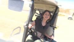 Attractive young girl backs out golf cart Stock Footage
