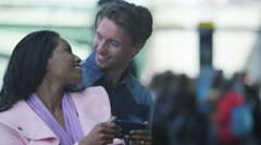4K Romantic mixed ethnicity couple looking at mobile phone outdoors in the city Stock Footage