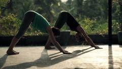 Two young girlfriends on terrace exercising yoga, doing sun salutation pose Stock Footage