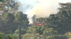 Building on fire in forest setting Stock Footage