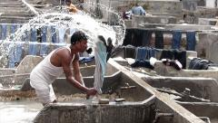 Man Washing Cloths at Mumbai Mahalaxmi Dhobi Ghat . slowmo - stock footage
