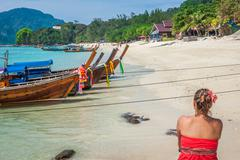 Woman on Tropical beach relaxing and watching longtail boats, Andaman Sea, Th - stock photo
