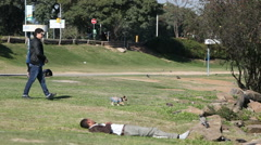 Man walks dog close to a homeless person laying on a sunny lawn in Porto Alegre. Stock Footage