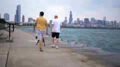 2 men walk dog by Lake Michigan with Chicago skyline on cloudy day Stock Footage