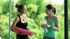 Two young, pretty girlfriends talking and drinking water while standing in garde Stock Footage