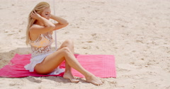 Sensual Woman Sitting on the Mat at the Beach Stock Footage
