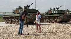 the journalist is doing a story on the background of tanks - stock footage