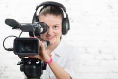 A pretty young woman with a professional  movie camera Stock Photos