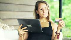 Young woman doing online shopping on tablet computer on terrace Stock Footage