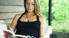 Young, beautiful woman reading book sitting on sofa on terrace Stock Footage