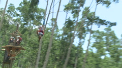 Attractive young Girl ziplining fast through trees Stock Footage