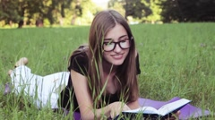 Beautiful Girl Reading a Book in The Park . Tired of reading. - stock footage