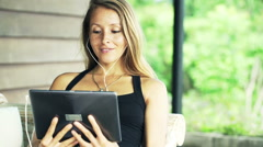 Pretty, young woman watching movie on tablet computer on sofa on terrace Stock Footage