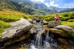 a little girl admiring a mountain creek - stock photo