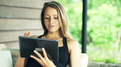 Young, pretty woman using tablet computer on sofa on terrace Stock Footage