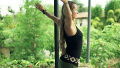 Young woman walking and stretching her arms in garden Stock Footage
