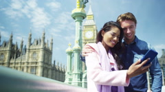 4K Romantic mixed ethnicity couple pose for a selfie in the city - stock footage
