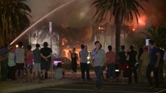 People walking at huge fire Stock Footage
