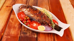main course: whole fryed sunfish on wood - stock footage