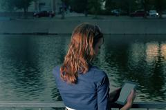 Redhair student female work tablet computer near lake in campus park Stock Photos