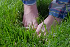 Bare feet in fresh spring grass - stock photo