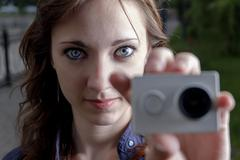 Young women with action camera in hand closeup. Peoples journalism concept - stock photo