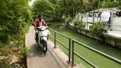 Motorbike run on concrete pathway of canal, green algal bloom water Stock Footage