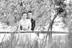 Married couple posing on wooden bridge bw - stock photo