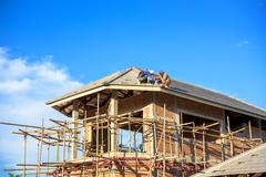 Stock Photo of labor working in construction site for roof