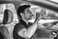 Young man driving his car while drinking alcohol - stock photo