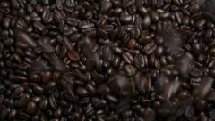 Coffee falling from above onto more roasted coffee beans below. Stock Footage