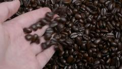 Hand drops some roasted coffee onto more beans. Stock Footage