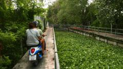 Motor scooter with two people rush along narrow concrete path at canal bank Stock Footage