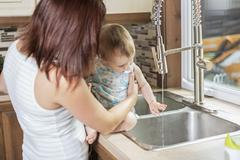 Young mother and her adorable toddler daughter in kitchen Stock Photos