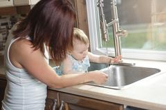 Young mother and her adorable toddler daughter in kitchen - stock photo