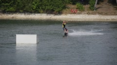 Skier Man in Helmet is Cable Skiing by Lake Surface Man Slides Close to a - stock footage