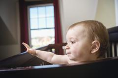 beautiful baby in a crib at home - stock photo