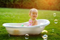 little girl sitting in the bath - stock photo