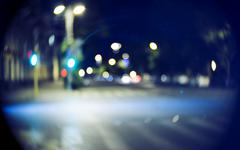 Blurred street at night time. Vintage looking shot made with old lens Stock Photos