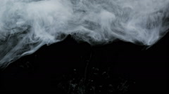 Veil of ink on black background floating slowly trough space, close up Stock Footage